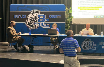 New Butler County Superintendent Robert Tuck, far left, works during a school board meeting July 14.