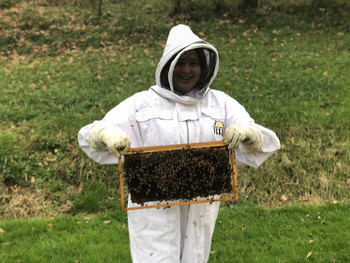 Picture of Emma Stevens wearing a beekeepers outfit and holding a rack from her hive filled with bees.