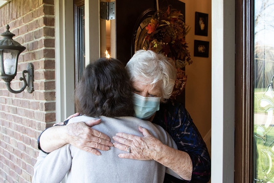 Two women hug at the front door of a brick house.