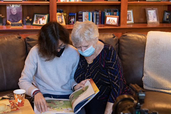 Two women sit on a couch looking through a picture book.