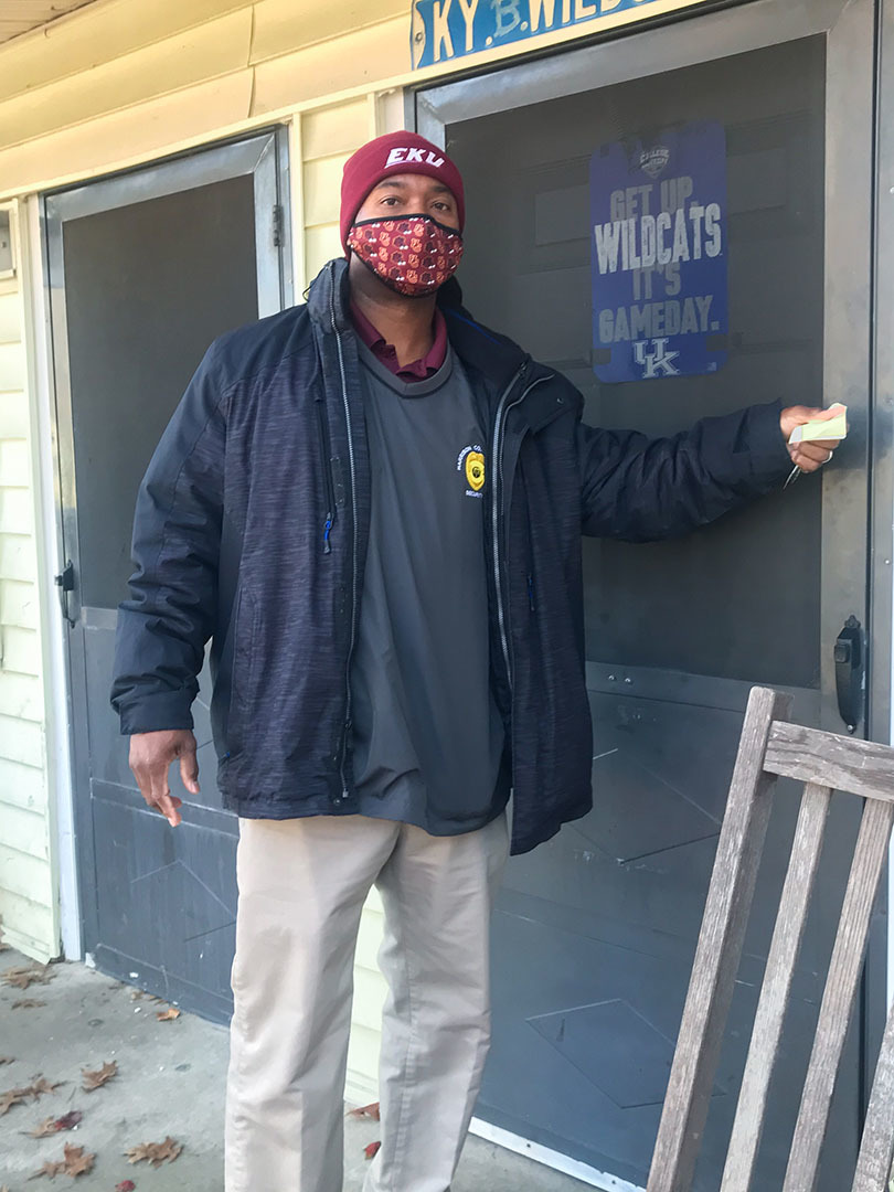 A man wearing a face covering knocks on the front door of a house.