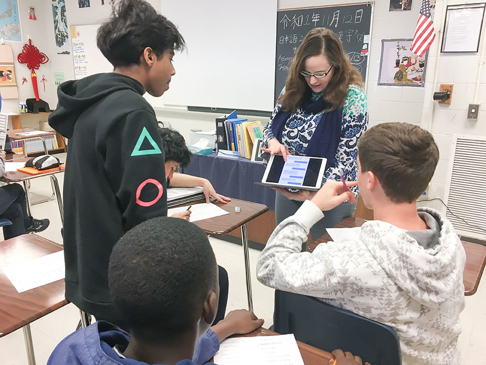 Elena Kamenetzky, a Japanese teacher at Eastern High School, holds up a tablet as she works with students in her classroom.