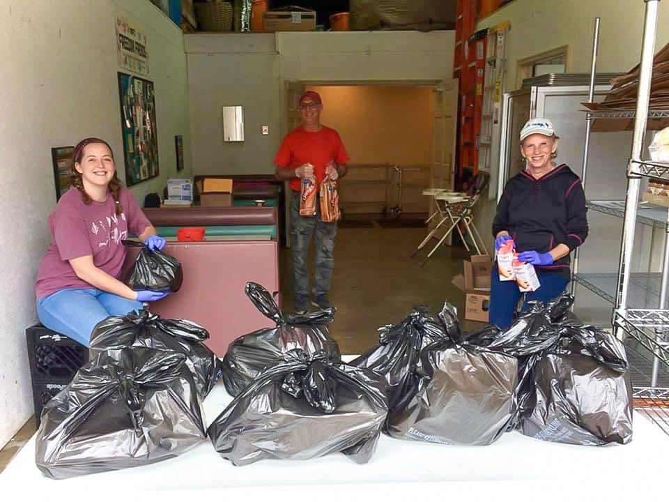 One woman and two men stand behind a group of garbage bags filled with food.