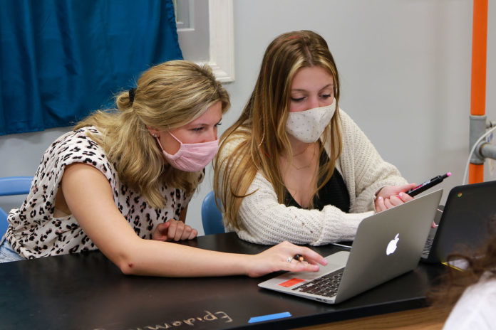Picture of teacher and a student working on a computer together, both are wearing face masks.