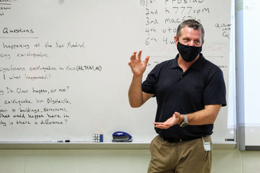 Picture of a man inside of a classroom wearing a face mask, talking and gesturing with his hands.