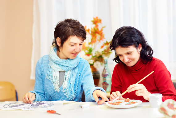 Two women painting at a table