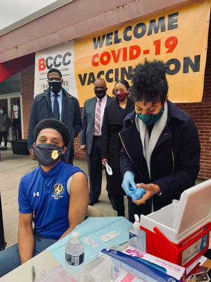 Mayor Brandon Scott getting vaccinated at BCCC by Dr. Dzirasa