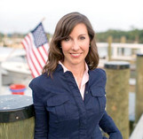 Photo of Sec. Haddaway-Riccio on dock in front of American flag