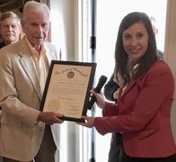 Photo of secretary presenting award to man
