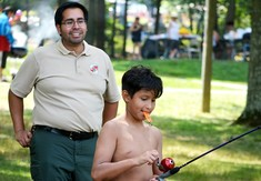 Photo of ranger helping boy learn to cast a fishing pole