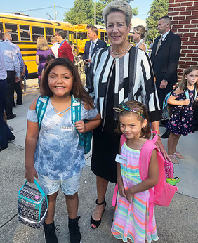 Dr. Salmon with two students standing and smiling outside of Waugh Chapel Elementary School on the first day of school 2018