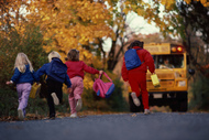 Stock image of children running towards a school bus on a fall day