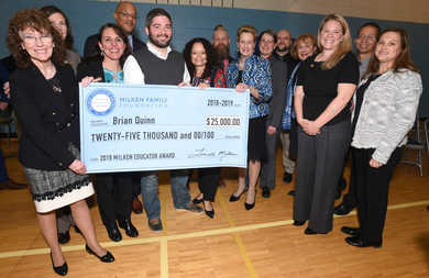 Maryland Milken Award Winner, Brian Quinn, smiles and holds up large cash prize check for $25,000
