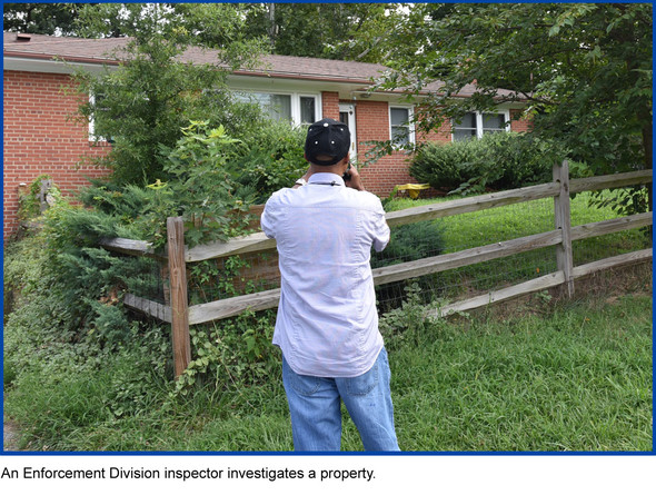 An Enforcement Division inspector investigates a property, inspector taking photos of tall grass and weeds