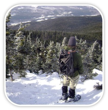 Snowshoer looking over a snow covered wooded valley and mt. range.