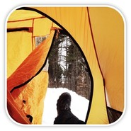 View out a golden tent flap door with booted leg extending toward the snow.