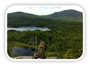 Photo showing view beyond a hikers stretched out legs form a rocky perch above a forested mountain view.