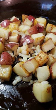 Homefried red potatoes, cubed, in skillet.