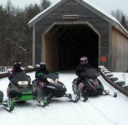 Snowmobile riders take a break near a covered bridge.
