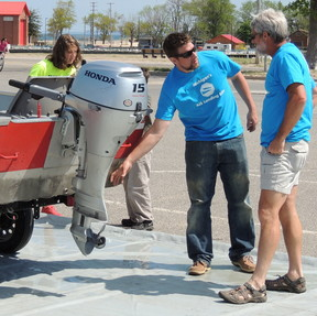A Landing Blitz volunteer at a previous event in Manistee discusses with a boater the importance of cleaning, draining and drying his boat to avoid spreading invasive species from one water body to another.