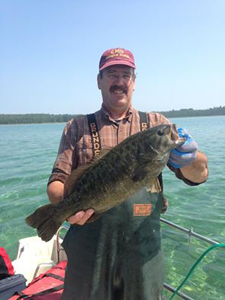 Tagged smallmouth bass being held by DNR employee