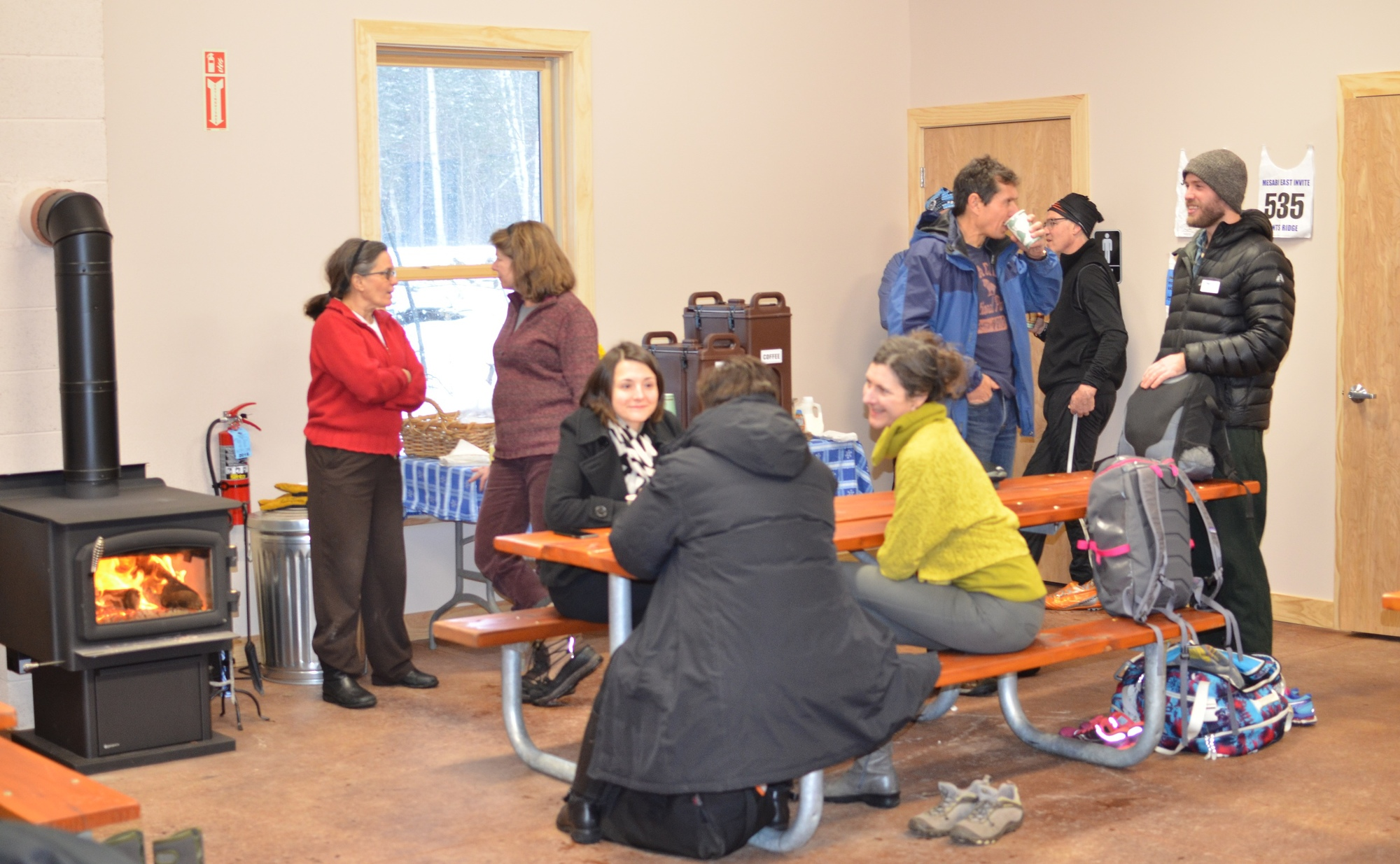 Visitors to the Blueberry Ridge Ski Pathway in Marquette County warm-up inside the facility after a ribbon-cutting ceremony. Outside, the temperature