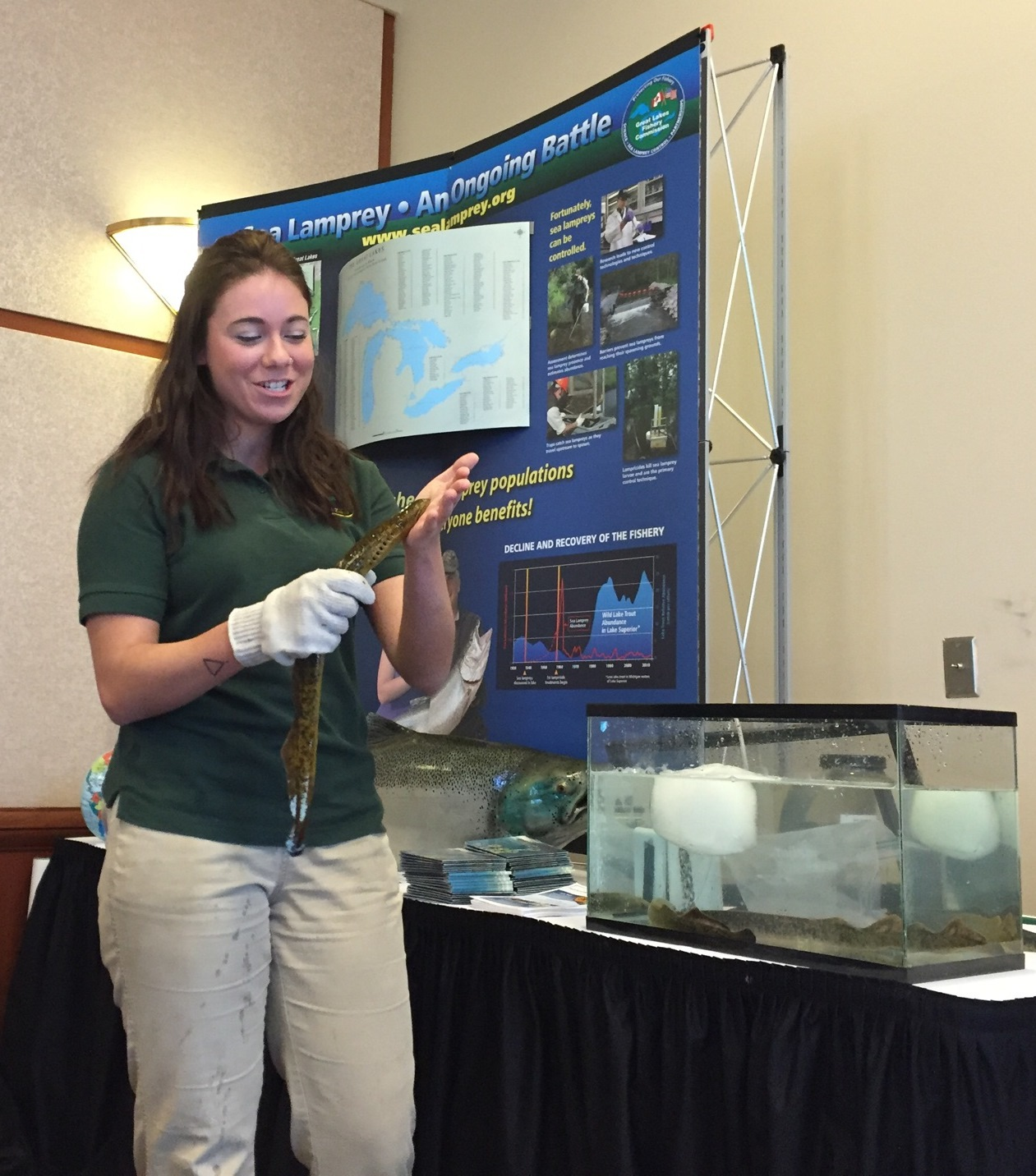 Tori Frailey, a senior biology student at Grand Valley State University, holds a live sea lamprey during her dad's presentation.
