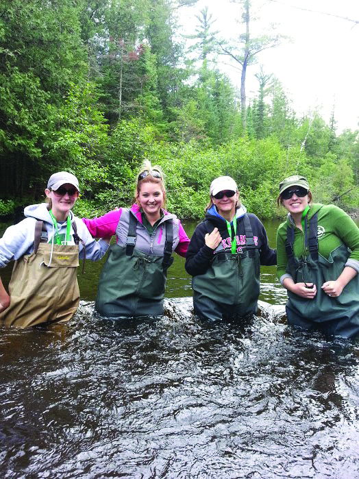 Four teachers wearing waders are standing in a stream at the Academy of Natural Resources, their first such waders experience.