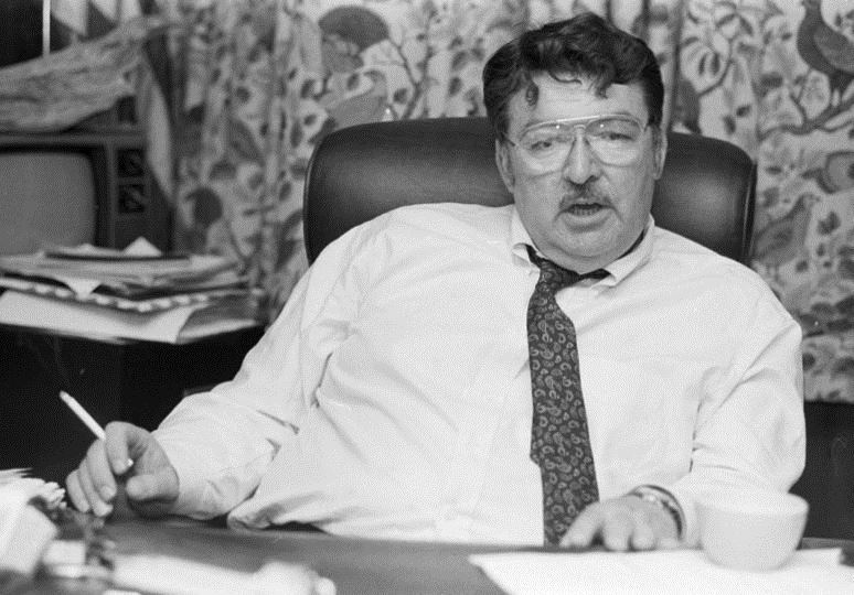 A black-and-white photo shows Tom Washington sitting behind his desk. Washington is the former director of the Michigan United Conservation Corps.