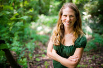 Photo shows a smiling Lisa Rose near a woods.