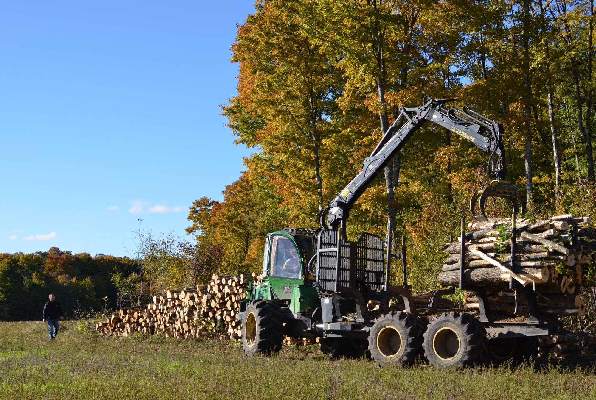 Against a blue autumn sky, logs are being moved on a Mackinac County logging operation.