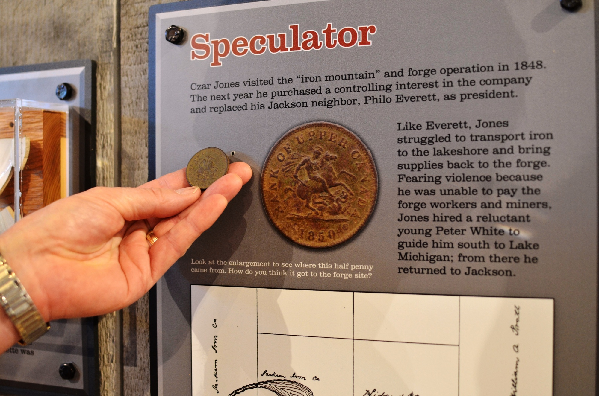 A half-penny artifact from the Carp River Forge is shown next to an exhibit display that discusses the coin.