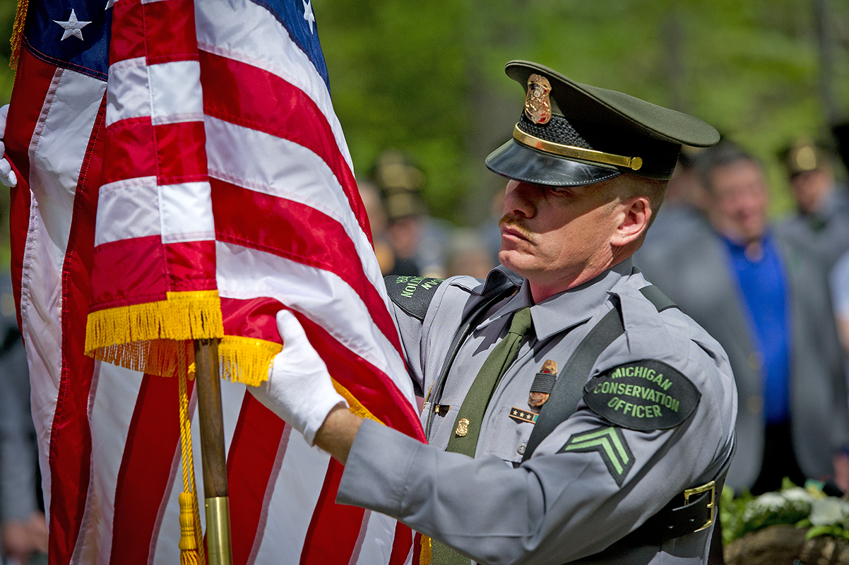 A Michigan conservation officer with an American flag at a fallen officers' memorial dedication ceremony.
