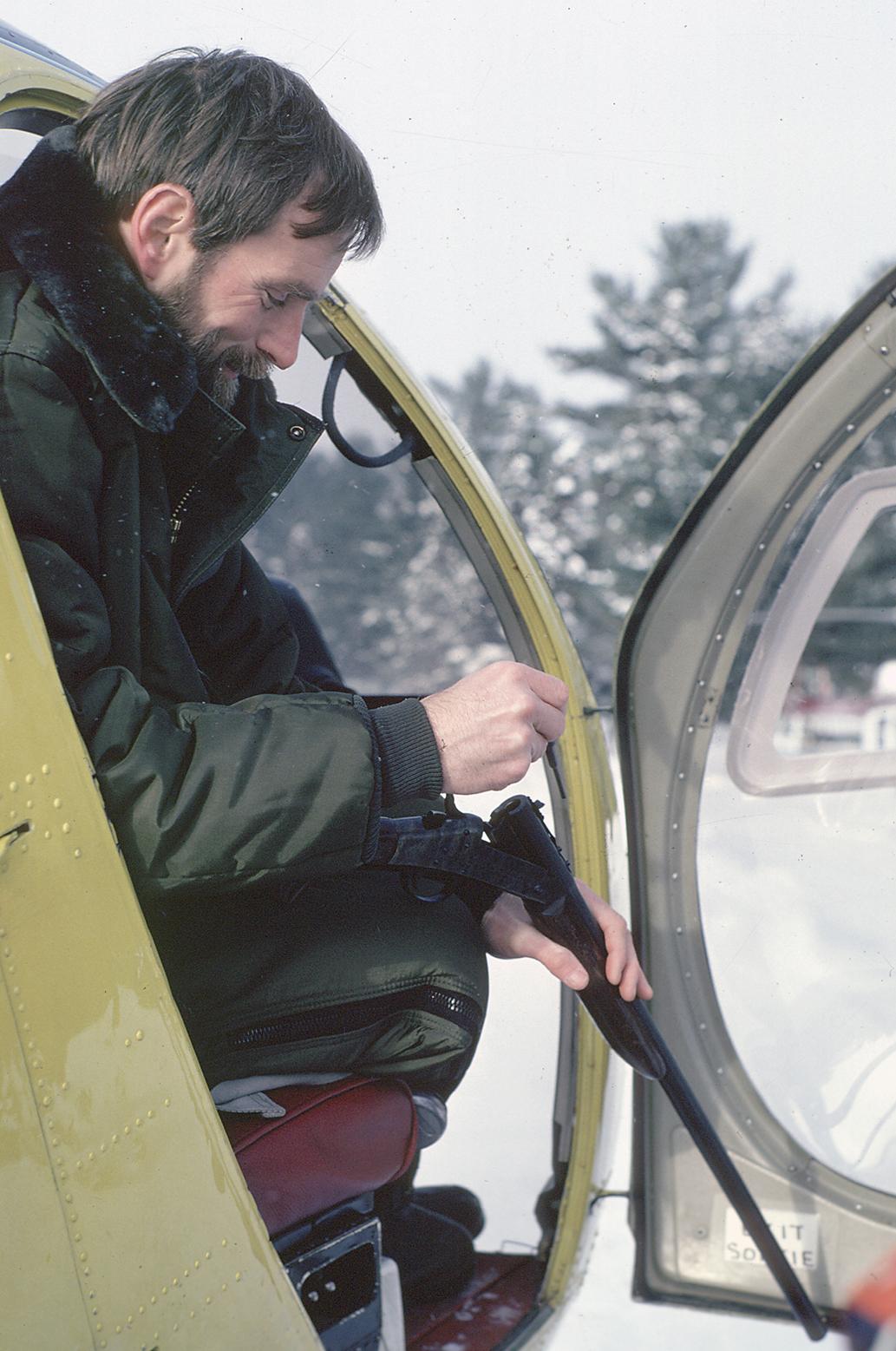 Michigan Department of Natural Resources wildlife veterinarian Steve Schmitt loads tranquilizing darts into a rifle.
