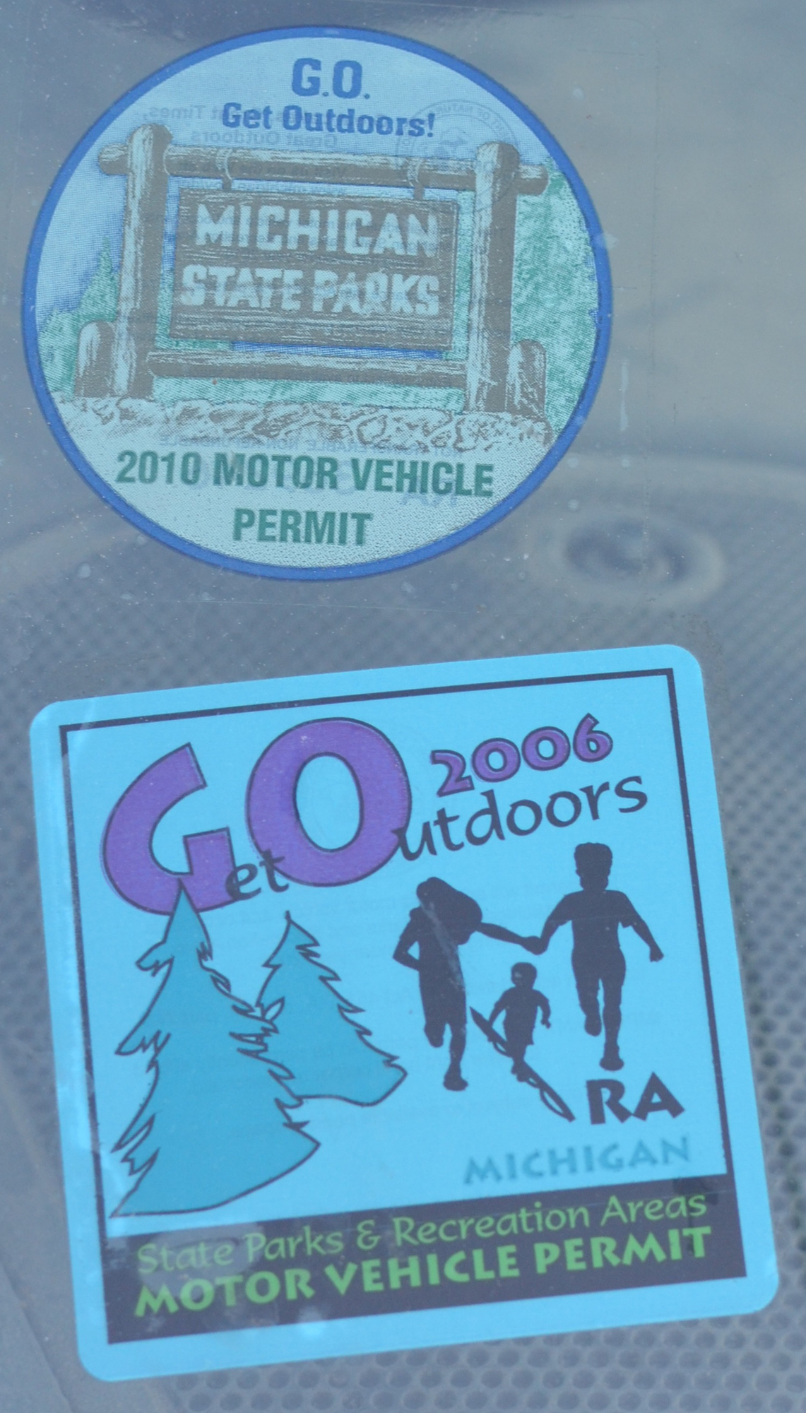 A couple of old Michigan Department of Natural Resources park permits still affixed to a windshield.