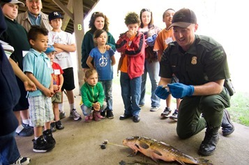 Kids watch a conservation officer explain the parts of a fish