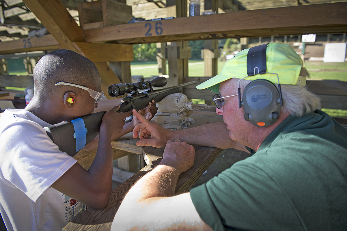 Pontiac Lake Shooting Range officer Warren Silverstein assists a young man with a .22 caliber youth model rifle.