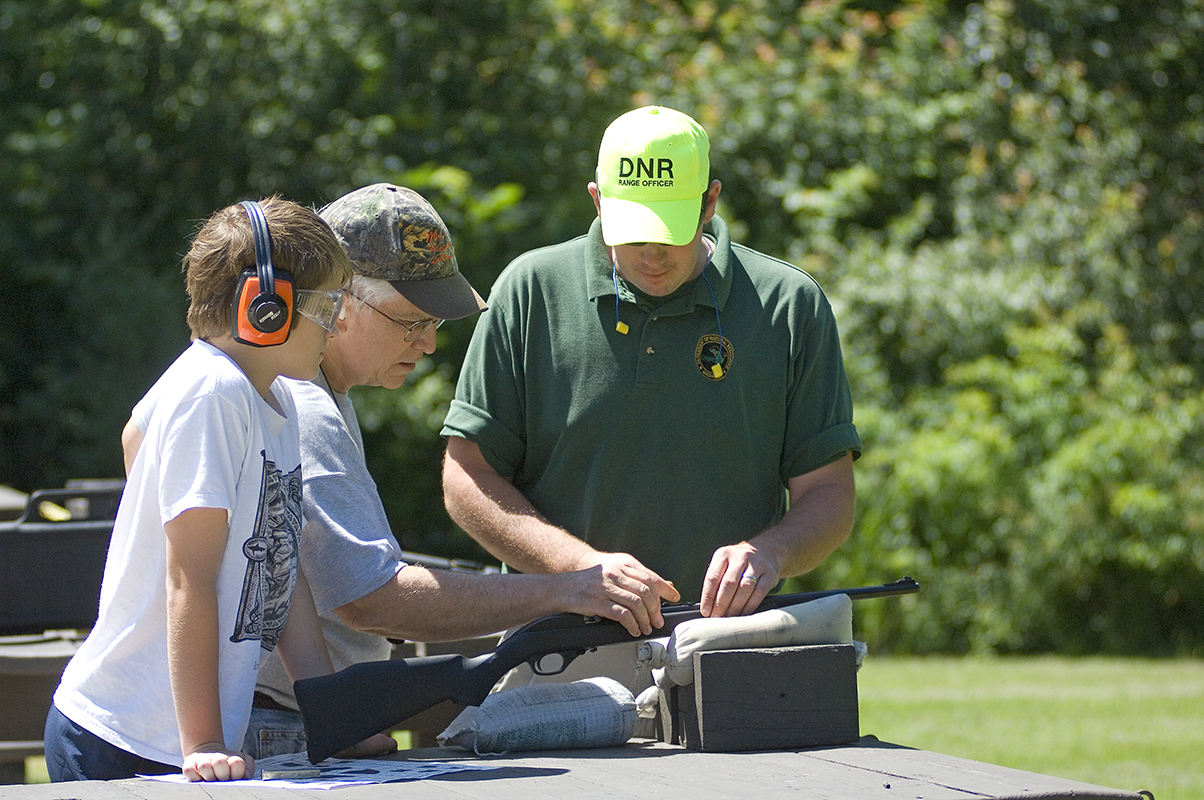 Ortonville Shooting Range attendant Charlie Brauer helps move the rear sight on a new .22 rifle a grandfather recently gave to his grandson.