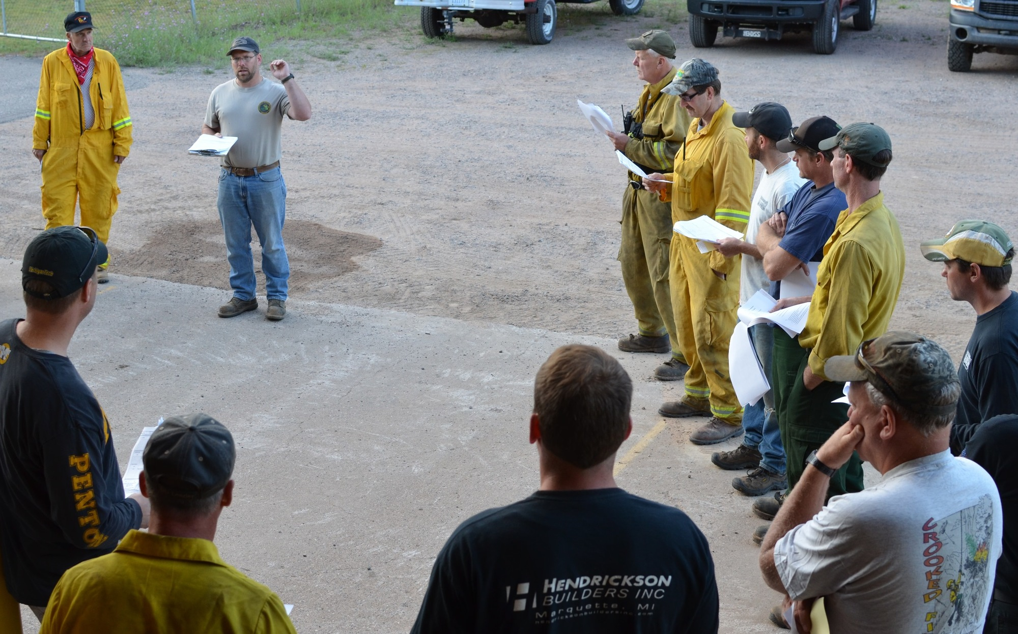 Pete Glover, second from left, initial Michigan Department of Natural Resources incident commander on the County Road 601 Fire, briefs firefighters.
