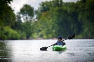 woman paddling in kayak on river