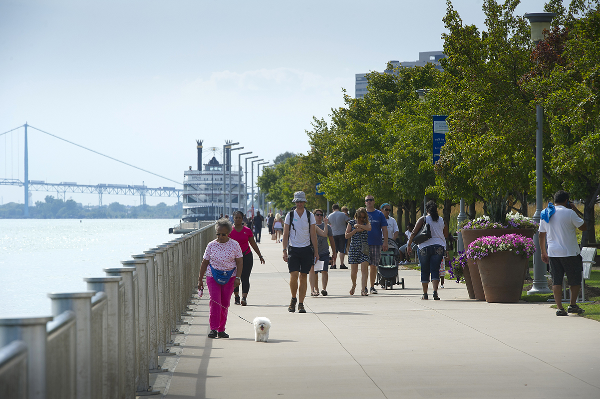 Walkers enjoy the day along the Riverwalk in Detroit.