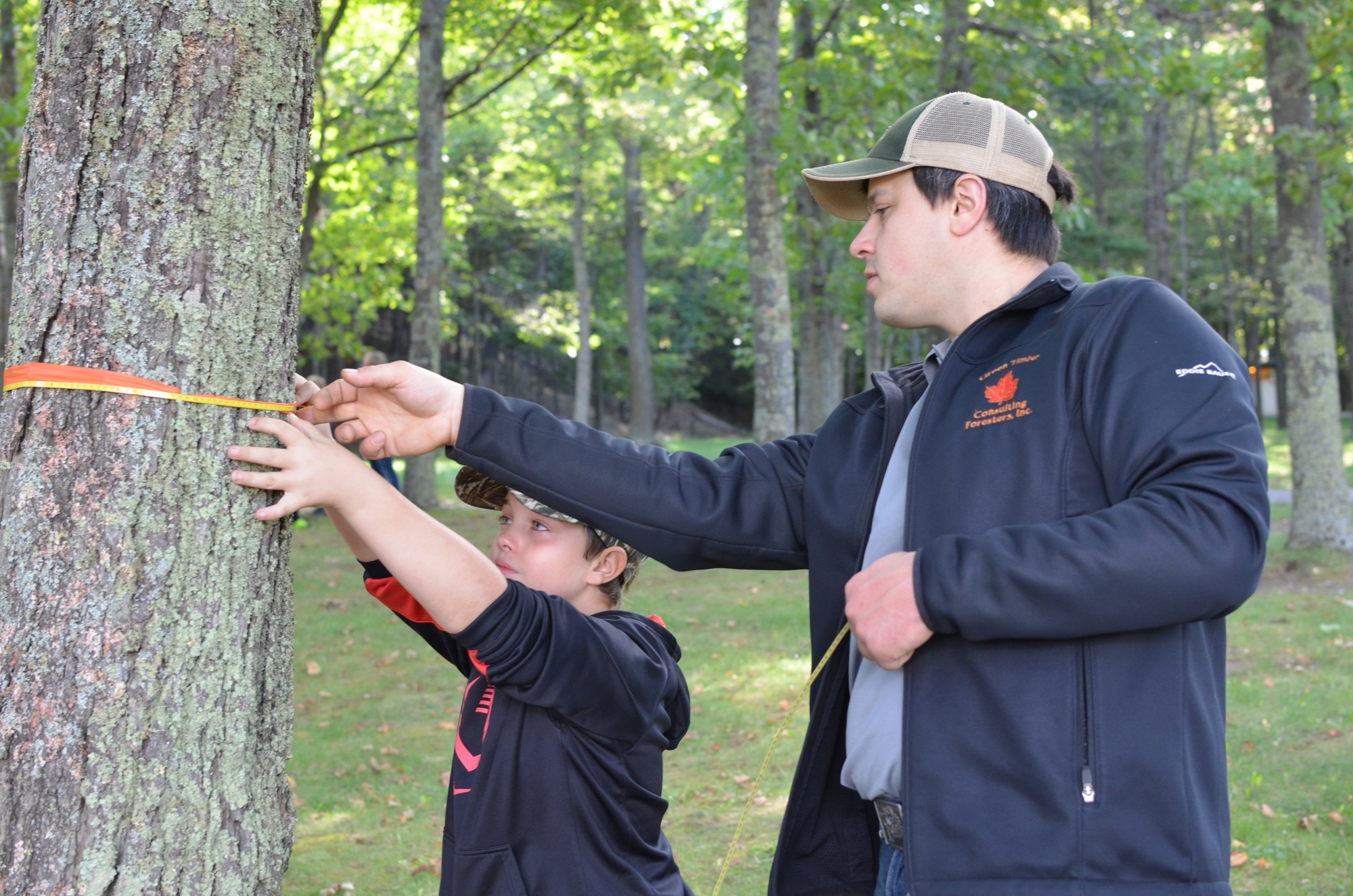 Mike Schreiber, a consulting forester with Green Timber Consulting Foresters, Inc., shows student Brandyn Hintsala how to measure a tree.