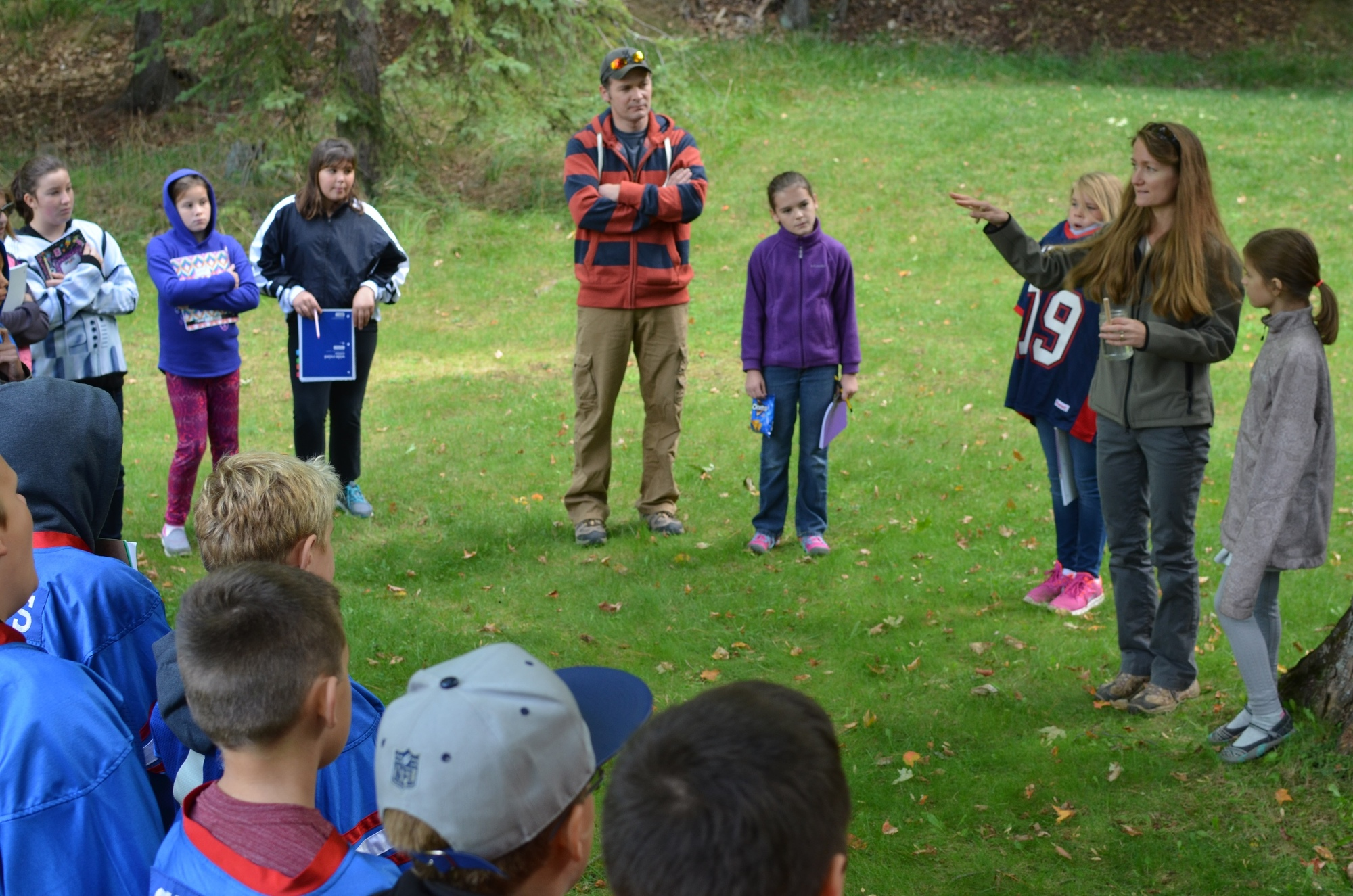 Michelle Miller, an environmental educator, discusses forest products and properties of trees with students at Presque Isle Park in Marquette County.