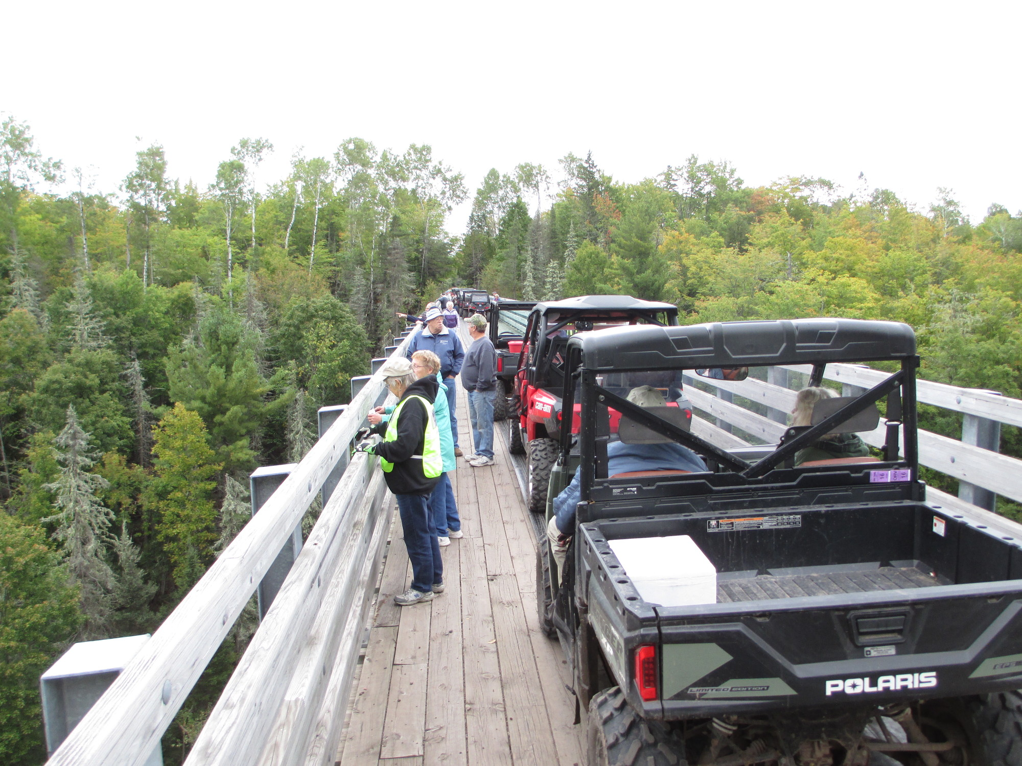 Off-road vehicle riders with the MI-TRALE senior ride stop to take a look over the trestle bridge over Agate Falls.