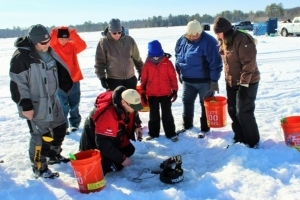 Ice fishing clinic instructor teaches students on frozen lake