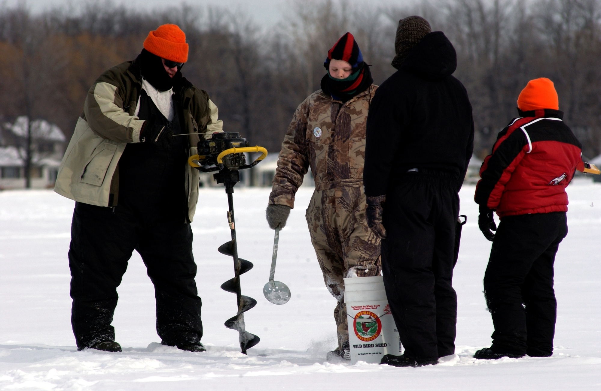 Anglers ready with an auger and ice scoop ice fish on a Michigan lake.