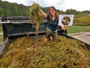 woman kneeling atop a truckbed full of frogbit, an invasive species