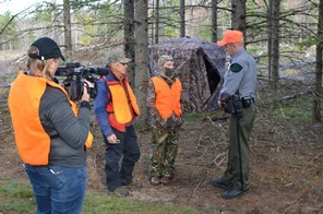 conservation officer talks to two deer hunters while being filmed for Wardens TV show