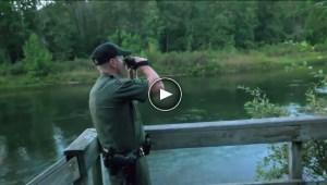 conservation officer looks over lake through binoculars in video still frame