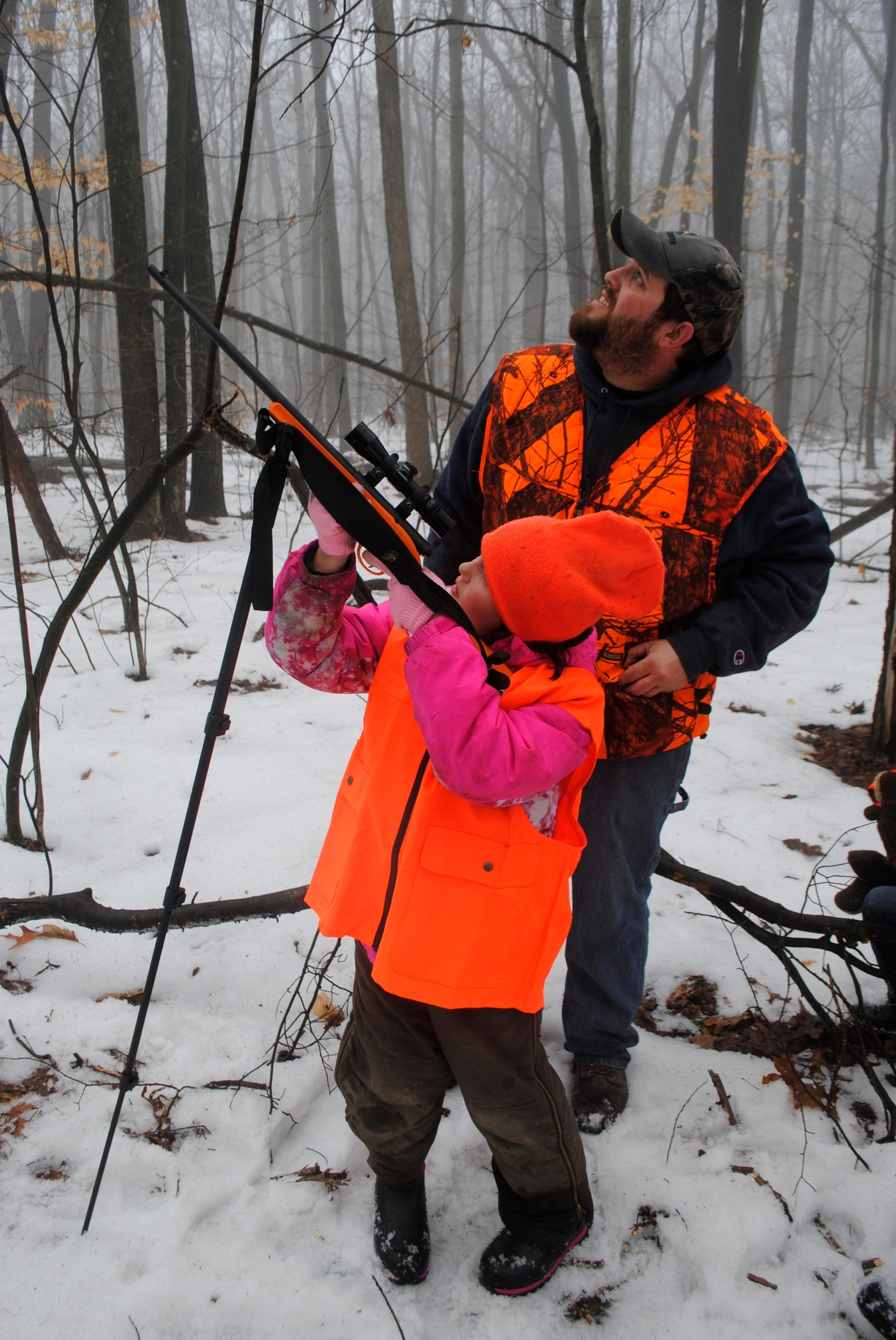 Destiny Ery takes aim at a squirrel with the help of her dad, Charles.